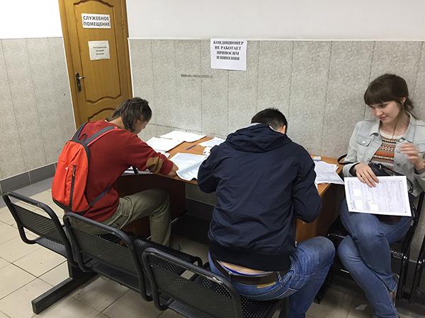Люди заполняют бланки регистрации в ФМС Санкт-Петербурга